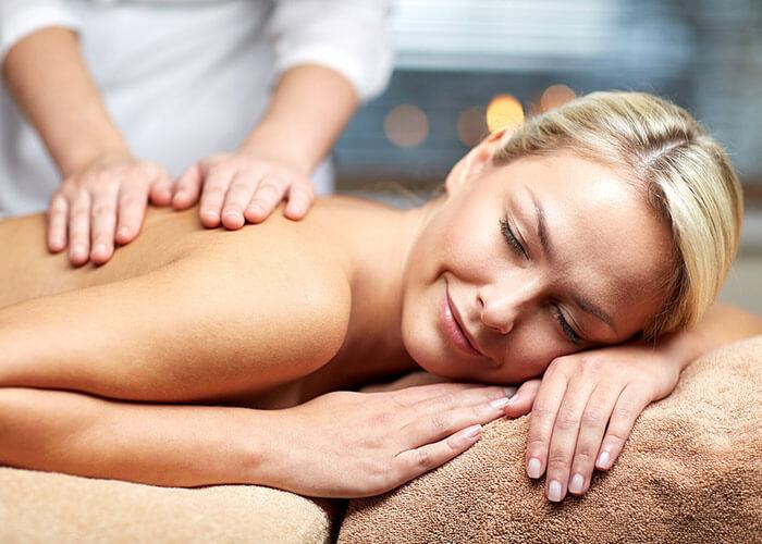 Woman enjoying a massage during a getaway in Marblehead, MA