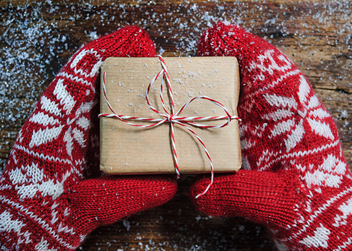 Hands with red mittens holding a small gift