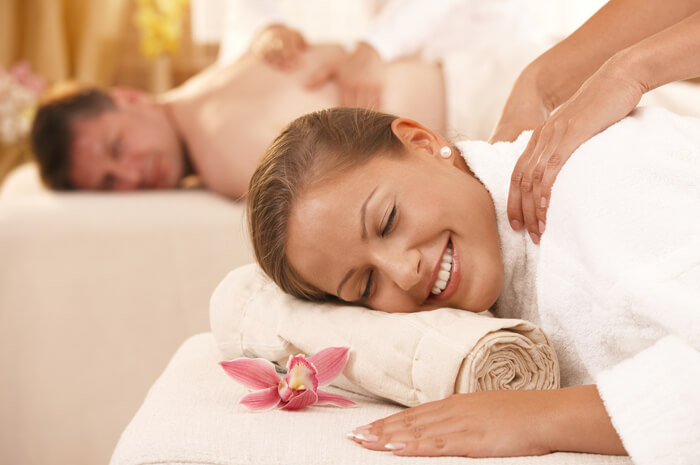 Couple getting a massage on white towels