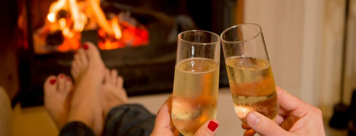 Two glasses of Champagne with two set of feet being warmed by a fire in the fireplace