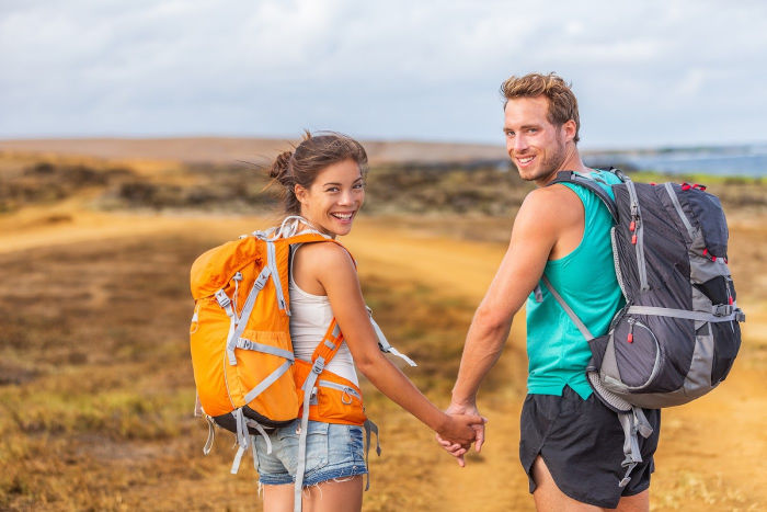 Young couple in shorts and tank tops on a hike near the ocean with backpacks on